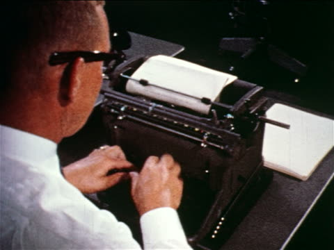 1960 close up over-the-shoulder man typing on manual typewriter at desk / newspaper office / documentary - 1960 stock videos & royalty-free footage