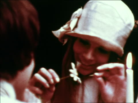 vídeos de stock e filmes b-roll de 1969 close up over-the-shoulder man watching hippie woman in hat pull petals off flower / greenwich village, nyc - hippie