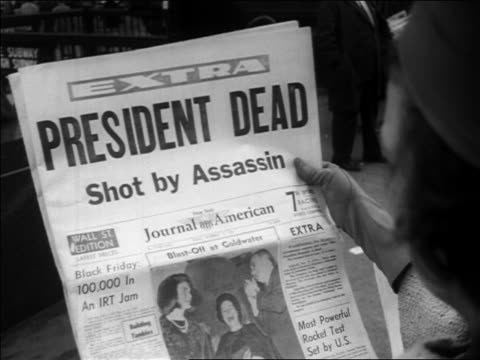 b/w 1963 close up overtheshoulder newspaper headlines president dead shot by assassin / kennedy's assassination - attentat auf john f. kennedy stock-videos und b-roll-filmmaterial