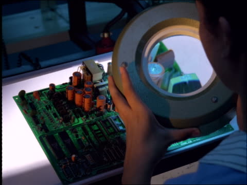close up over-the-shoulder of person looking through magnifying glass at circuit board in factory / brazil - magnifying glass stock videos & royalty-free footage