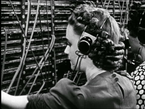 b/w 1946 close up over-the-shoulder telephone operator plugging in wires at switchboard / industrial - customer service representative stock videos & royalty-free footage