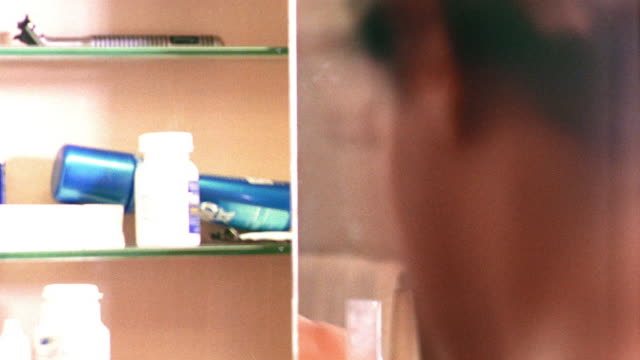 close up over-the-shoulder time lapse man brushing teeth, gargling + wiping face with towel in reflection of mirror