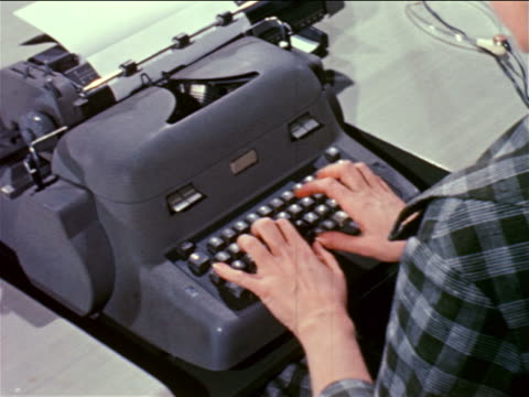 1961 close up over-the-shoulder woman's hands typing on typewriter / industrial