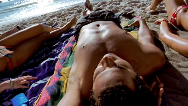 close up pan across two women in bikinis and one man sunbathing on beach - sonnenbaden stock-videos und b-roll-filmmaterial