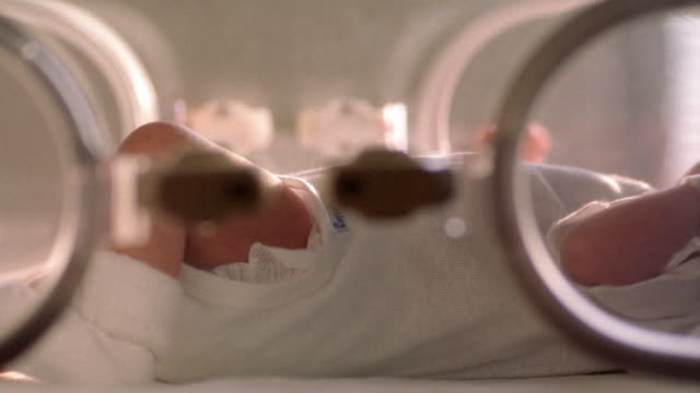 close up pan baby moving arms and legs inside hospital incubator - babies only stock videos & royalty-free footage
