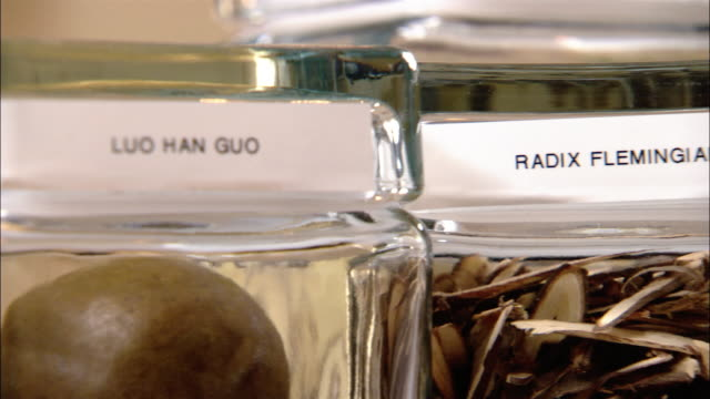 close up pan back and forth between labels on glass jars of herbs - chinese herbal medicine stock videos and b-roll footage