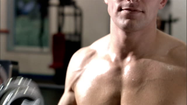 close up pan bare chest of young man lifting weights in health club - abdominal muscle stock videos & royalty-free footage