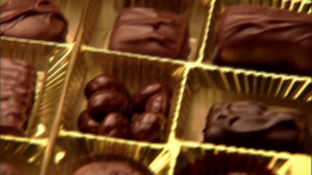 close up pan box of chocolates/ hand taking piece of chocolate - panning stock-videos und b-roll-filmmaterial