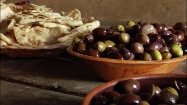 close up pan bread and olives in bowls on table/ israel - tavolo video stock e b–roll