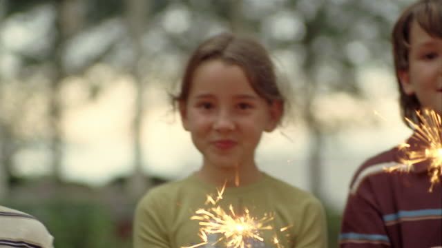 vídeos y material grabado en eventos de stock de close up pan children holding sparklers smiling at cam - bengala fuego artificial