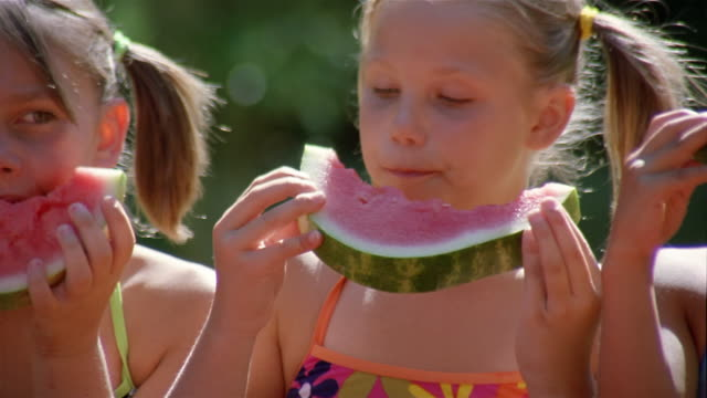 Close up pan children in swimsuits eating slices of watermelon / New York