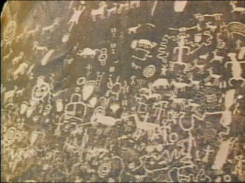 1975 close up pan elaborate carvings of human and animal figures on rock / mesa verde, colorado - mesa verde national park stock videos & royalty-free footage