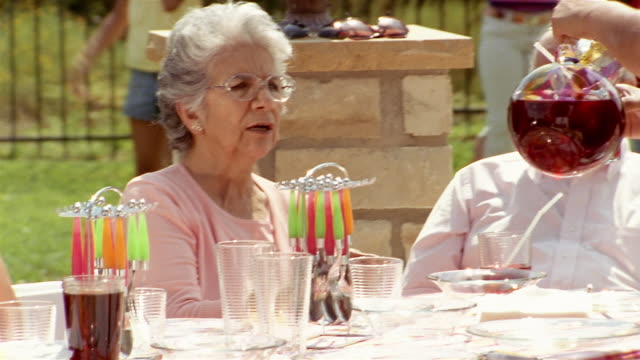 close up pan family members attending barbecue in backyard - big family stock videos & royalty-free footage