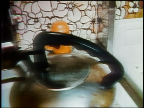 1975 close up pan from feminist sticker on stove / hands doing dishes in sink / tilt up woman / narrator audio - 女性の権利点の映像素材/bロール