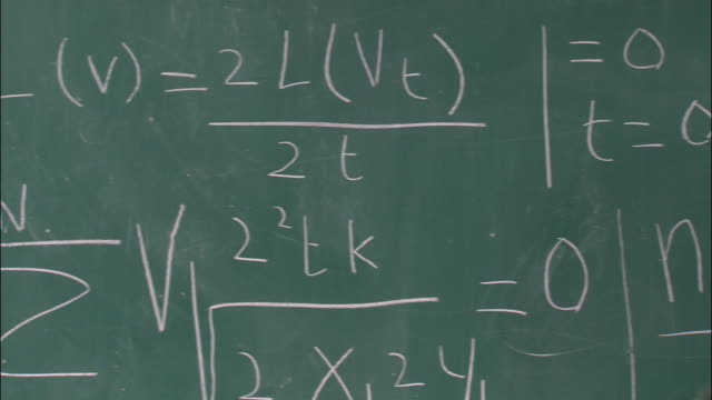 Close up pan girl at chalkboard trying to figure out mathematical problem