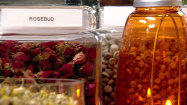 close up pan glass jar of rosebuds and glass jar of gingerroot - chinese herbal medicine stock videos and b-roll footage