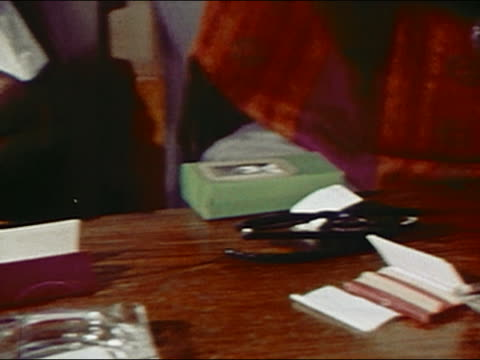 1970 close up pan hands of two men rolling joints / audio - drug abuse stock videos & royalty-free footage