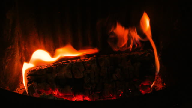 close up pan left onto a blazing wood log on an open fireplace - flammable stock videos & royalty-free footage