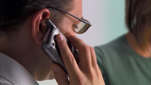 Close up pan man at phone as woman watches/ man and woman high-fiving