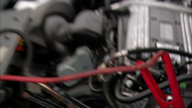 close up pan man attaching jumper cables to car battery - ström bildbanksvideor och videomaterial från bakom kulisserna