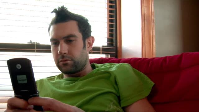 stockvideo's en b-roll-footage met close up pan man texting on cell phone/ new jersey - hanenkam haardracht