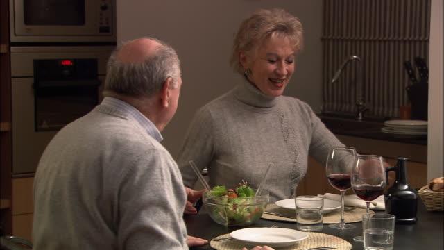 close up pan mature woman carrying salad bowl to dinner table / medium shot woman salting and adding oil to salad / tossing and serving salad to senior man - salad oil stock videos & royalty-free footage