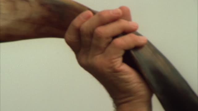 Close up pan of a Jewish man blowing on a shofar