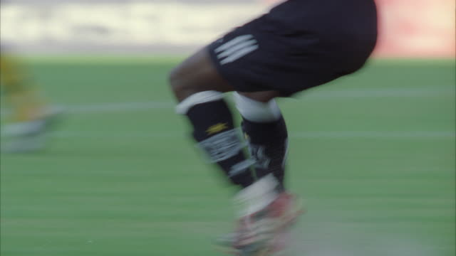 close up pan of soccer player's legs running after the ball on the field - ハウテング州点の映像素材/bロール