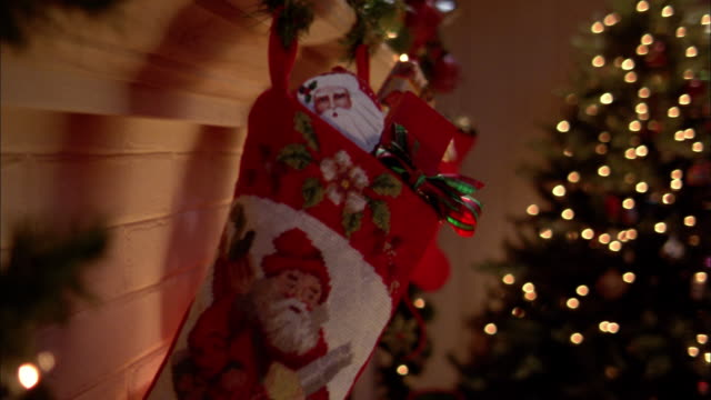 Close up pan of stockings hanging from fireplace w/Christmas tree in background