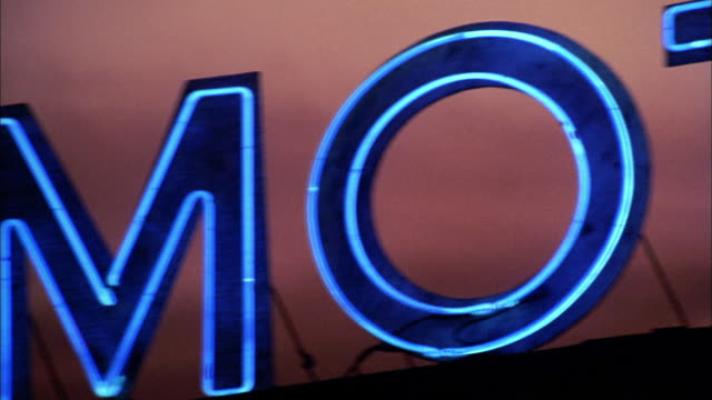 close up pan over neon motel sign - motel stock videos & royalty-free footage