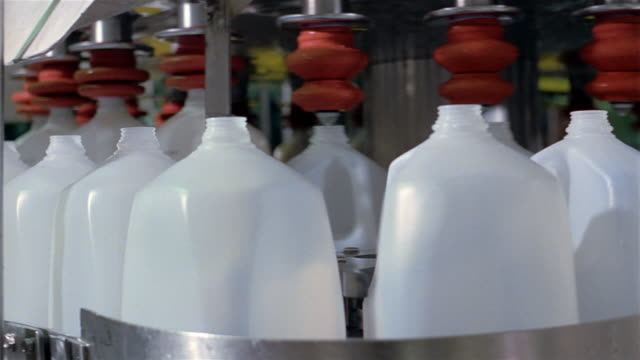 close up pan plastic jugs being filled with milk and sealed at dairy factory - dairy product stock videos & royalty-free footage