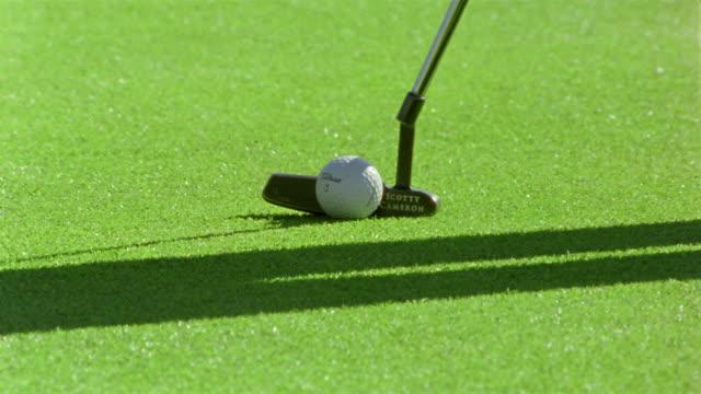 vídeos y material grabado en eventos de stock de close up pan putter hitting golf ball / ball missing hole / black diamond ranch, lecanto, florida - putt