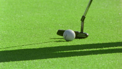 close up pan putter hitting golf ball into hole / man reaching down and retrieving ball / lecanto, florida - putting stock videos & royalty-free footage