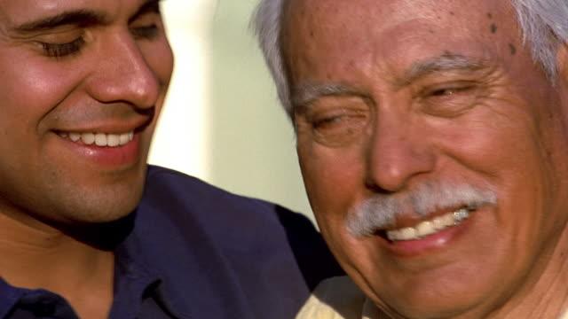 Close up pan senior man and younger man smiling
