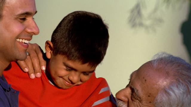 Close up pan senior man, young boy and younger man smiling
