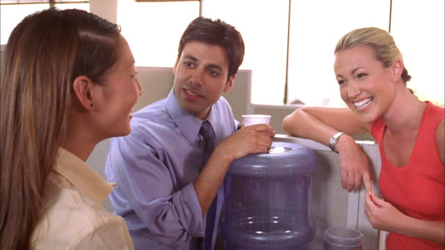 vidéos et rushes de close up pan shaky three office workers standing near water cooler and talking / zoom in zoom out office workers - fontaine
