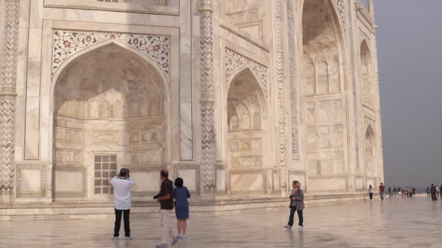 a close up pan shot across the famous white marble tomb of taj mahal in agra, india, a unesco world heritage site - taj mahal stock videos and b-roll footage
