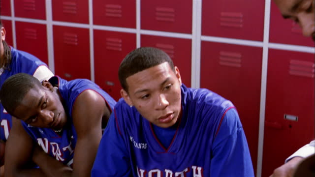 vidéos et rushes de close up pan teenage basketball players listening to coach in locker room - personne sportive