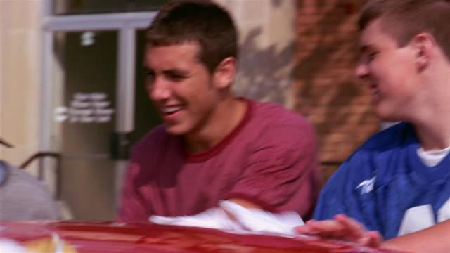 close up pan teenagers washing car - biltvätt bildbanksvideor och videomaterial från bakom kulisserna