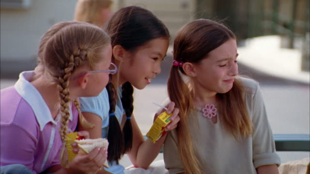 close up pan three girls eating lunch and looking at boy on bench on school playground - hair band stock videos & royalty-free footage