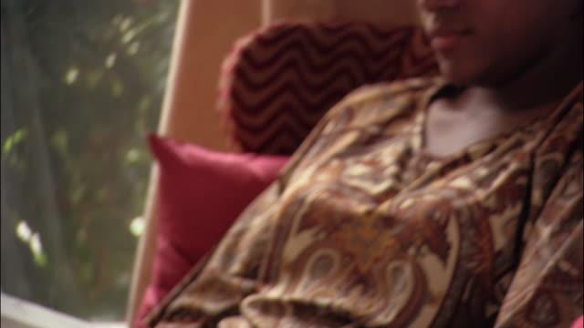 vidéos et rushes de close up pan woman sitting in chair by window and reading - prendre sur les genoux