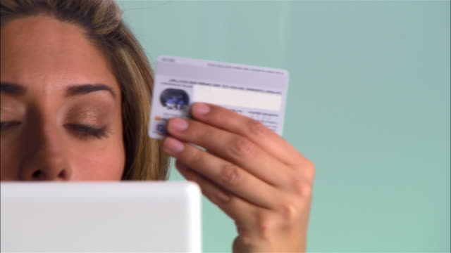 close up pan woman's face obscured by computer monitor as she holds up credit card and types in the number - electronic organiser stock videos & royalty-free footage
