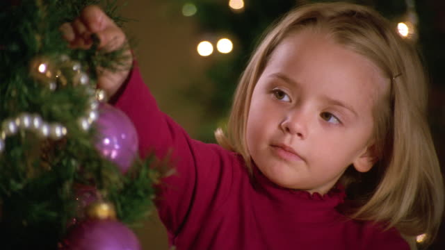stockvideo's en b-roll-footage met close up pan young girl hanging ornament on christmas tree - kerstboom versieren
