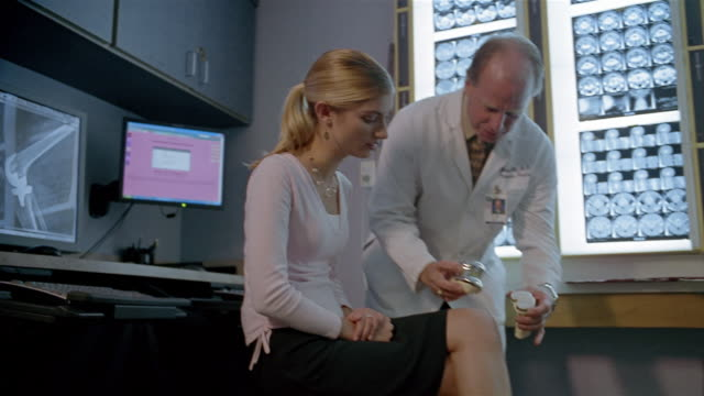 close up pan zoom out x-rays and flat screen monitor / low angle medium shot zoom in doctor demonstrating artificial knee for patient - inarcare la schiena video stock e b–roll