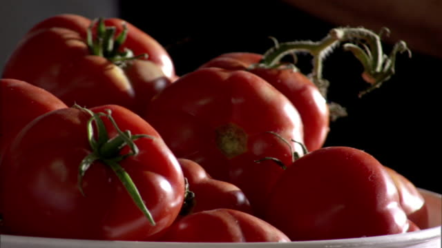 close up pan-left - a chef selects tomatoes from a bowl. / sicily, italy - reaching stock videos & royalty-free footage