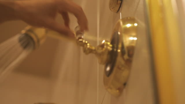 Close Up pan,left , A hand turns a faucet and water sprays from a shower head. /