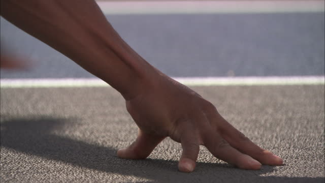 close up pan-left - an athlete seeks proper hand position before a sprint - atletico video stock e b–roll