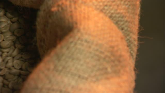 close up pan-left - raw coffee beans fill a burlap sack /  georgia, united states - 荒い麻布点の映像素材/bロール