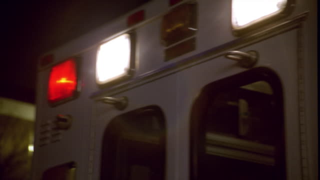 close up panning amblulance with flashing lights on - ambulance stock videos & royalty-free footage
