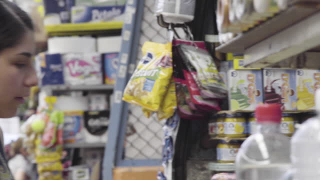 close up. panning and then fixed shot. a young lady buys goods at a grocery stand at the interior of mercado alamos market. close up of a seller... - black hair stock videos & royalty-free footage